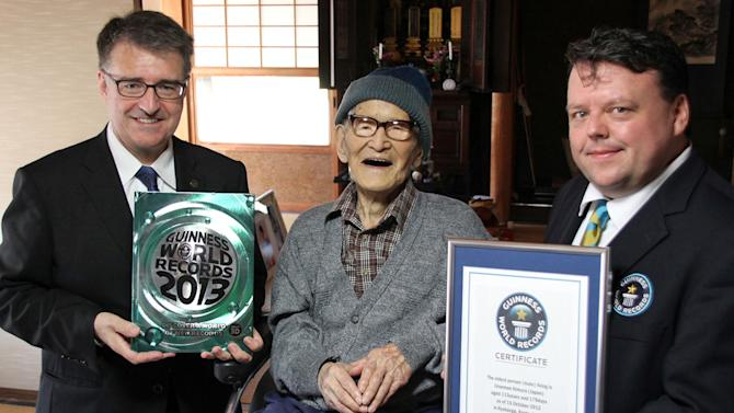 ADDS AGE - FILE - In this file photo taken Oct. 15, 2012 and released by Kyotango City, Jiroemon Kimura, center, poses with Guinness World Records Editor-in-Chief Craig Glenday, right, and Guinness World Records Asia-Pacific Representative Frank Foley after Kimura was presented with the certificate of the world's oldest living man at his home in the city, Kyoto Prefecture, Japan. Japanese media report that Kimura died of natural causes at a hospital in Kyotango early Wednesday, June 12, 2013 at the age of 116.  (AP Photo/Kyotango City, File) EDITORIAL USE ONLY