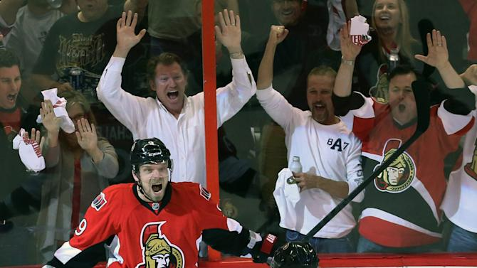 As fans, background, react, Ottawa Senators Milan Michalek (9) celebrates his goal against the Pittsburgh Penguins with teammate Daniel Alfredsson (11) during first-period NHL hockey playoff game action in Ottawa, Ontario, Wednesday, May 22, 2013. (AP Photo/The Canadian Press, Fred Chartrand)