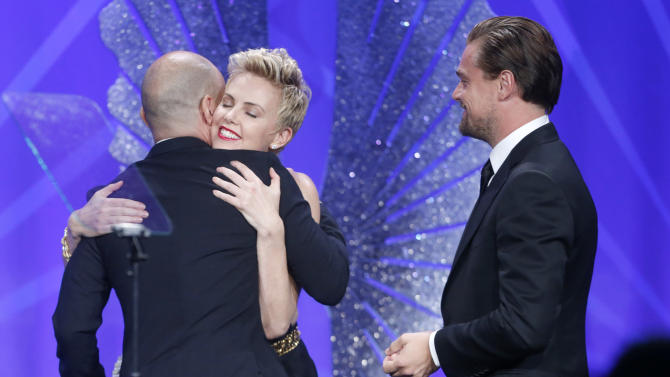Honoree Steve Warren accepts the Stephen F. Kolzak Award from actors Charlize Theron and Leonardo DiCaprio at the 24th Annual GLAAD Media Awards at the JW Marriott on Saturday, April 20, 2013 in Los Angeles. (Photo by Todd Williamson/Invision/AP)