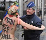 An activist from Femen is taken away by police as she demonstrates against Russian President Vladimir Putin, in Brussels, on December 21, 2012. Some have called the movement a new brand of feminist activism