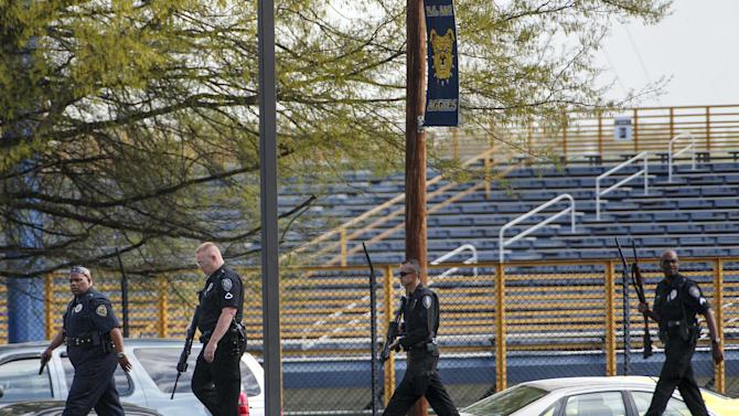Greensboro and North Carolina A&T State University police walk along Sullivan Street on the university campus after there were reports of a man with a rifle on the campus, Friday, April 12, 2013, in Greensboro, N.C. The university updated its website Friday morning to advise that students should stay inside and lock their doors and windows. (AP Photo/News & Record, Jerry Wolford)