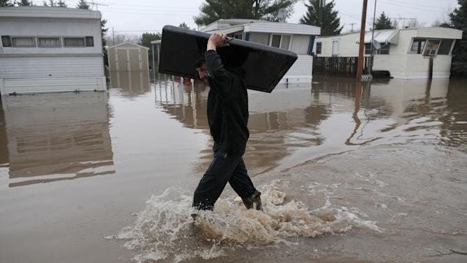 Tim Fitzwater, of Geneseo Ill., carries a flat-screen television out of his father's mobile home in Geneseo on Thursday, April 18, 2013, after the Geneseo Creek pushed out of its banks by heavy rain, flooded the park and threatened several businesses. (AP Photo/The Dispatch, Todd Mizener)  QUAD-CITY TIMES OUT, MANDATORY CREDIT