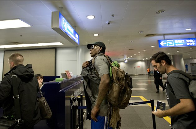 Former NBA star Dennis Rodman, center, walks to the check in counter at the departure hall of Beijing Capital International Airport in Beijing Tuesday, Feb. 26, 2013. Rodman, three members of the Harl