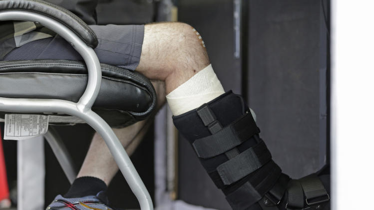 NASCAR driver and team co-owner Tony Stewart props his injured leg