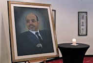 <p>A candle burns beside a mural of Ethiopia's late Prime Minister, Meles Zenawi, during a government press conference announcing his death in Addis Ababa on August 21. Deputy Prime Minister Hailemariam Desalegn, 47, will take over interim power.</p>