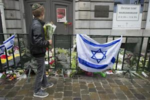 A Jewish boy stands with flowers by an Israeli flag …