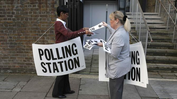 Polling station workers place signs outside a polling station in Islington, in readiness for voting in Britain's general election, in London