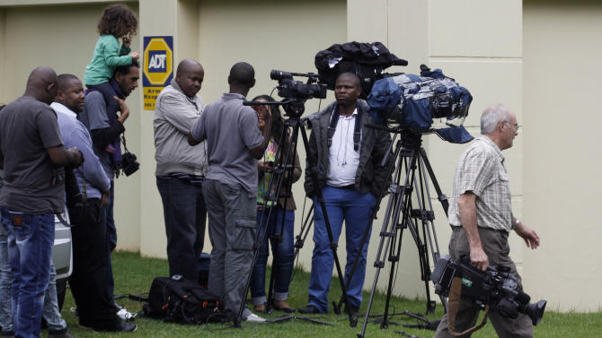 Members of the media gather outside the home of former South African president Nelson Mandela after he was discharged from a hospital on Wednesday evening after nearly three weeks of treatment, in Johannesburg, South Africa, Thursday, Dec. 27 2012. The doctors treating former South African leader Nelson Mandela believe he should remain in Johannesburg for now to be close to medical facilities that can provide care to the 94-year-old, the government said Thursday. (AP Photo/Denis Farrell)