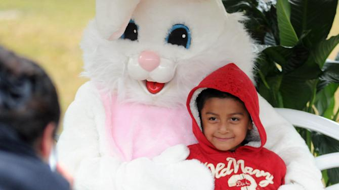 Maria Cardona, left, takes a picture of her son Diego Cardona while posing with the Easter Bunny at the 4th annual Leland Egg Hunt at Brunswick River Park in Leland Saturday, March 30, 2013.  (AP Photo/The Star-News, Matt Born)