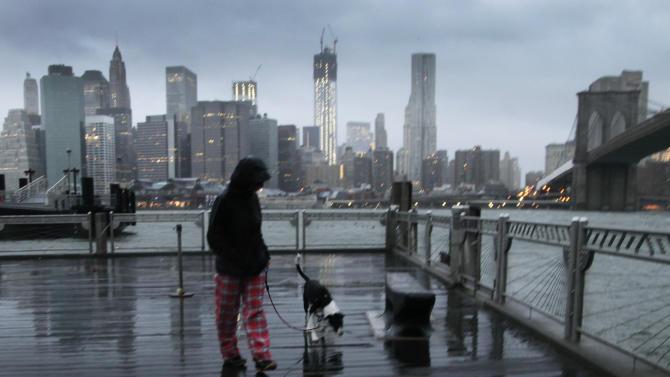 Vanessa Pumo walks her dog Bella as wind and rain from Hurricane Sandy arrive, Monday, Oct. 29, 2012 in Brooklyn, N.Y. Behind her is the Manhattan skyline and Brooklyn Bridge, right. (AP Photo/Mark Lennihan)