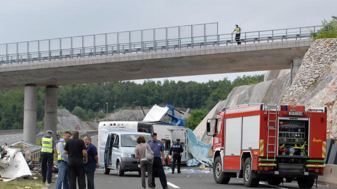 Police survey the scene of the bus crash near Gospic, Croatia, Saturday, June 23, 2012. At least seven Czech tourists were killed and 44 injured in a bus crash on a major highway in Croatia early Saturday, police said. The accident happened some 200 kilometers (124 miles) south of Zagreb, on the highway connecting the Croatian capital with the central Adriatic coastal city of Split. (AP Photo) CROATIA OUT