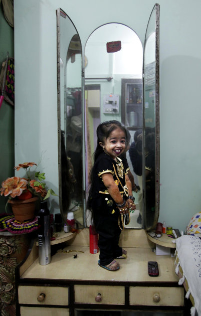 Indian Jyoti Amge, 18, who stands at 61.95 centimeters (2 feet), poses in front of a mirror as she prepares for a press conference with Guinness World Records at her home in Nagpur, India, Friday, Dec