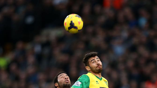 Norwich City's Bradley Johnson, right, and Tottenham Hotspur's Mousa Dembele compete for the ball during their English Premier League soccer match at Carrow Road, Norwich, England, Sunday, Feb. 23, 2014