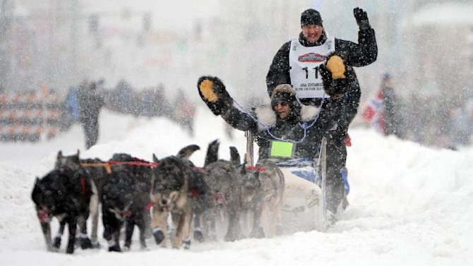 2011 Iditarod champion John Baker and his Iditarider wave during the ceremonial start of the Iditarod Trail Sled Dog Race, Saturday, March 3, 2012 in Archorage, Alaska. (AP Photo/Anchorage Daily News, Bob Hallinen)