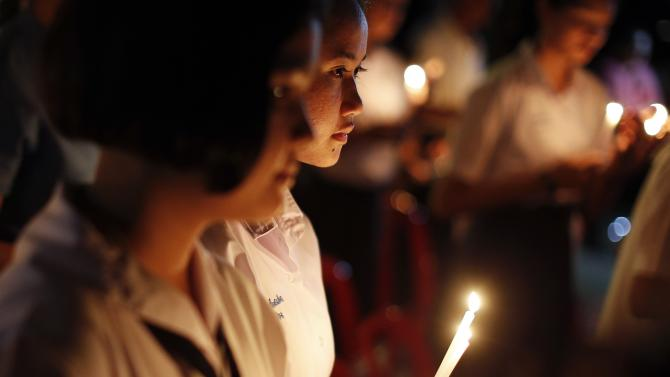 People light candles as survivors, local residents and visitors gather for a ceremony for victims of 2004 tsunami in Ban Nam Khem