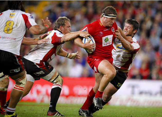 Queensland Reds prop James Slipper (C) is tackled by Golden Lions players during their Super 15 rugby union match at Suncorp Stadium in Brisbane on May 19, 2012.  IMAGE STRICTLY RESTRICTED TO EDITORIA