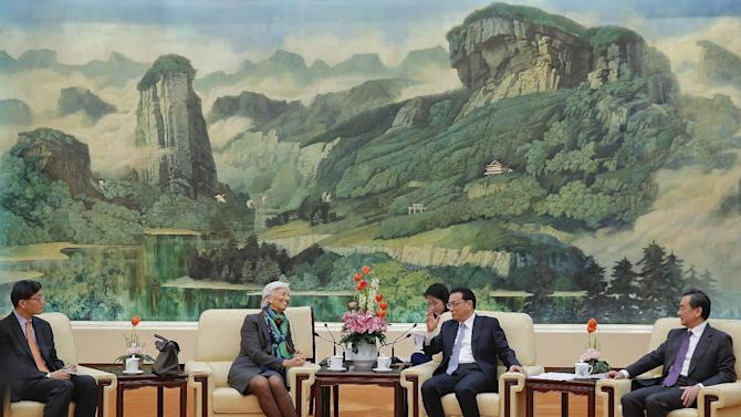In this March 23, 2015, photo, International Monetary Fund Managing Director Christine Lagarde, second from left, talks with Chinese Premier Li Keqiang, second from right, during a meeting at the Great Hall of the People in Beijing. Lagarde said Sunday that China's economic slowdown is legitimate and that Beijing can contribute to global prosperity. U.S. resistance to a Chinese-led Asian regional bank has left it isolated among its Asian and European allies and given some heft to China's frequent complaints that Washington wants to contain its rise as a world power.  (AP Photo/Lintao Zhang, Pool)
