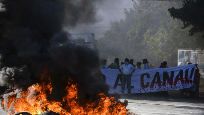 Residents burn tires at a blockade on the Pan-American highway  during the groundbreaking day of the $50 billion transoceanic waterway construction project predicted to rival the Panama Canal, in Managua, Nicaragua, Monday, Dec. 22. 2014.  The groundbreaking marked the start of some ancillary projects in Brito, a city about 5 kilometers (3 miles) from Nicaragua's Pacific coast where the first port will be built. Officials say the canal will be fully operational by 2019.(AP Photo/ La Prensa, Oscar Navarrete)