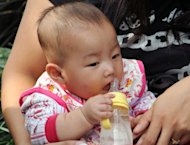 A Chinese baby drinks coconut milk mixed with water instead of baby formula in Shanghai. A Chinese dairy has been ordered to suspend production after a cancer-causing toxin was found in its infant formula, China's quality watchdog said Monday, in the country's latest milk scare