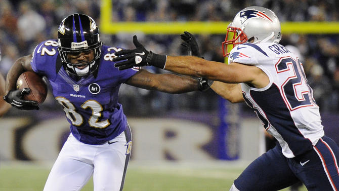 Baltimore Ravens wide receiver Torrey Smith, center, rushes between New England Patriots defenders Dont'a Hightower (54) and Steve Gregory in the second half of an NFL football game in Baltimore, Sunday, Sept. 23, 2012. (AP Photo/Nick Wass)