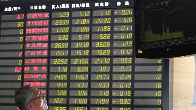 An investor watches the stock price monitor at a private securities company in Shanghai, China, Tuesday, May 14, 2013. Asian stock markets were mixed Tuesday in a lukewarm reaction to data showing that U.S. consumers revved up their retail spending last month. (AP Photo/Eugene Hoshiko)