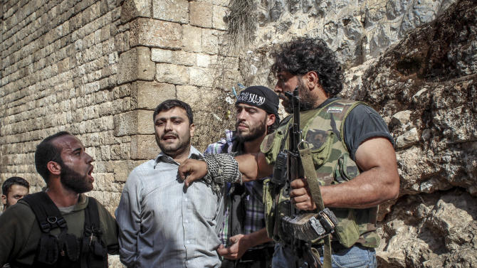 In this Tuesday, Oct. 30, 2012 photo, Free Syrian Army fighters shout at a captured suspected pro-Bashar Assad fighter in the town of Harem, Syria. Rebels say the man was killed shortly after this picture. Despite two weeks of attacking a Roman-era citadel in which pro-Assad militia are dug in, the rebels failed to secure the town. (AP Photo/Mustafa Karali)