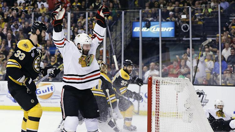 Chicago Blackhawks left wing Brandon Saad, center, celebrates a goal by Blackhawks center Michal Handzus, right, in front of Boston Bruins defenseman Zdeno Chara (33) during the first period in Game 4 of the NHL hockey Stanley Cup Finals, Wednesday, June 19, 2013, in Boston. (AP Photo/Elise Amendola)