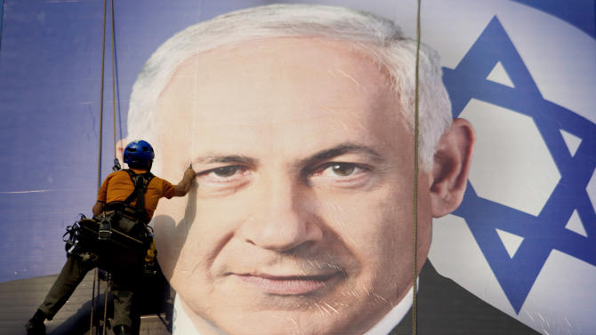 A worker hangs a huge poster with an  image of Israel's Prime Minister Benjamin Netanyahu overlooking the Ayalon freeway in Tel Aviv, Israel,Thursday, Jan. 17, 2013. Legislative elections in Israel will be held on Jan. 22, 2013. (AP Photo/Ariel Schalit)