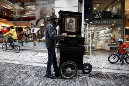 A man plays a laterna at a central market street of  Athens