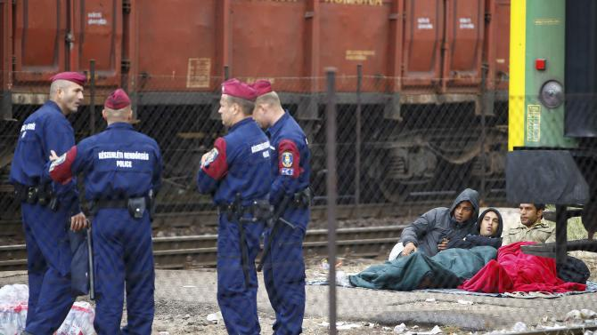 Hungarian police officers stand next to migrants at the Bicske railway station in Bicske