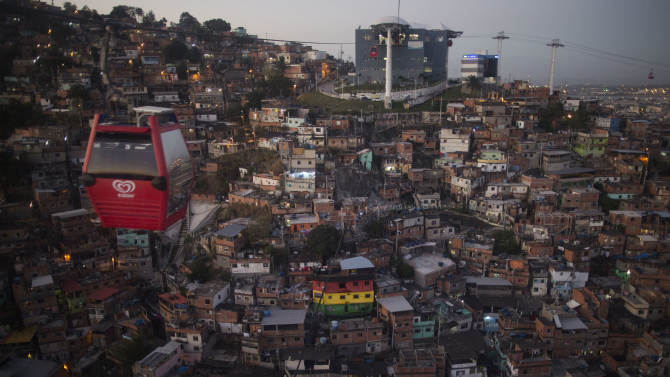 A cable car transports commuters over homes in the Complexo do Alemao shantytown in Rio de Janeiro, Brazil, Tuesday, Sept. 23, 2014. The cable car system that spans the Complexo do Alemão allows residents a faster commute and it has become a popular destination for foreign tourists on the weekend. (AP Photo/Leo Correa)
