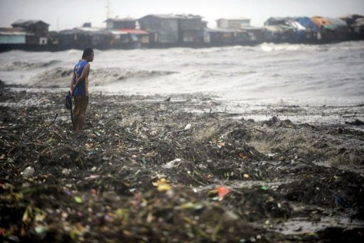 A man looks for usable materials amongst garbage washed up by strong waves caused by super-typhoon Nanmadol
