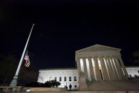 Capitol Hill police officers lower the U.S. flag at the Supreme Court in Washington D.C. after the death of U.S. Supreme Court Justice Antonin Scalia