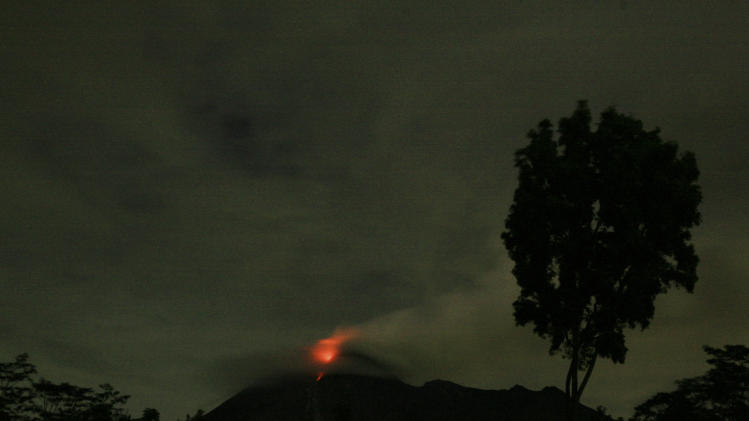 Lava glows from the crater of Mount Merapi as seen from Deles, Central Java, Indonesia, Tuesday, Nov. 2, 2010.  International airlines halted flights to airports near Indonesia's most dangerous volcano Tuesday, as fiery lava lit the rumbling mountain's cauldron and plumes of smoke blackened the sky.(AP Photo/Binsar Bakkara)