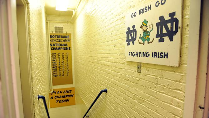 """FILE - In this Nov. 21, 2011, file photo, the hallway between the locker room and the field at Notre Dame stadium shows the sign """"Play like a Champion Today"""" in South Bend, Ind. At a time when college football was generally considered the domain of eastern blue bloods, Notre Dame and Alabama were upstart teams that gave blue collar fans a chance to tweak the elite. About 90 years later, the Fighting Irish and Crimson Tide are the elite - two of college football's signature programs, set to play a national championship next Monday in Miami that could break records for television viewership. (AP Photo/Joe Raymond, File)"""