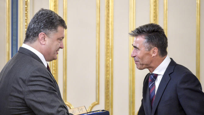 Ukrainian President Petro Poroshenko, left, greets NATO Secretary General Anders Fogh Rasmussen during their meting in Kiev, Ukraine, Thursday, Aug. 7, 2014. (AP Photo/Mykola Lazarenko, Pool)