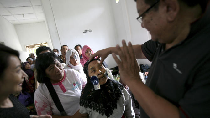 In this Sunday, Nov. 4, 2012 photo, a patient reacts after Dr. Sanduk Ruit, right, removed her eye patches following her cataract surgery at a military hospital in Padang Sidempuan, North Sumatra, Indonesia. Indonesians flocked to the hospital for free cataract surgery performed by a team led by Nepalese master surgeon Dr. Sanduk Ruit who is renowned for his high-volume assembly-line approach. During the eight-day eye camps held in two towns in North Sumatra, more than 1,400 cataracts were removed. (AP Photo/Binsar Bakkara)