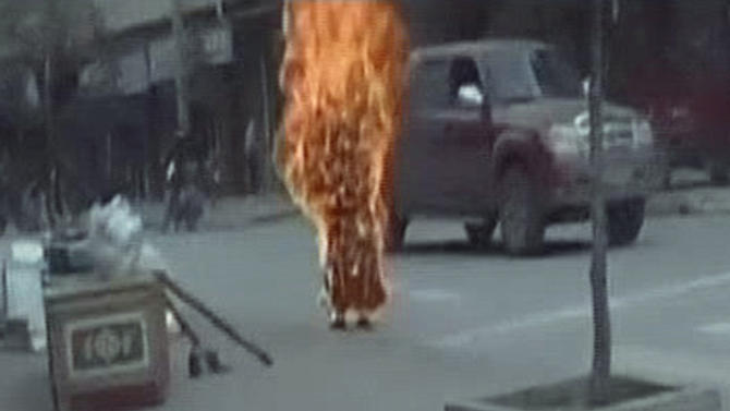 FILE - In this file image taken from Nov. 11, 2011 video footage released by Students For A Free Tibet via AP video purports to show Buddhist nun Palden Choetso engulfed in flames in her self-immolation protest against Chinese rule on a street in Tawu, Tibetan Ganzi prefecture, in China's Sichuan Province. Dozens of Tibetans have set themselves on fire over the past year to protest Chinese rule, sometimes drinking kerosene to make the flames explode from within, in one of the biggest waves of political self-immolations in recent history. (AP Photo/Students For A Free Tibet via AP video, File)