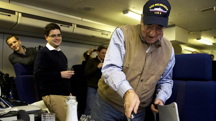 "The traveling staff on board the E-4B surprise U.S. Defense Secretary Leon Panetta with a cake that says ""arrivederci,"" in a celebration in honor of the last leg of his final overseas trip as secretary, en route to Washington, Saturday, Jan. 19, 2013. The plastic meat axe at right was a joke gift from the staff, at the secretary's reference to budget sequestration being a meat axe. (AP Photo/Jacquelyn Martin)"