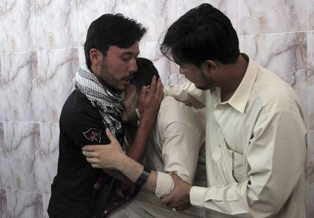 Men mourn the death of a relative, who was killed with two others by unidentified gunmen, in a hospital Quetta, Pakistan