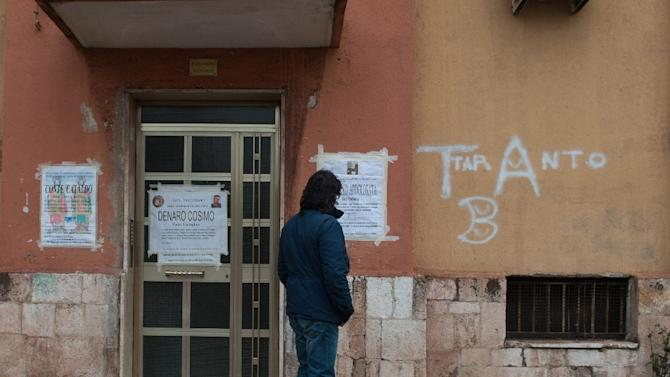 Fabio Matacchiera, an ecologist opposed to pollution by the Ilva steel plant, reads obituaries pasted at the entrance of a building in the Tamburi district on March 18, 2015 in Taranto, Italy