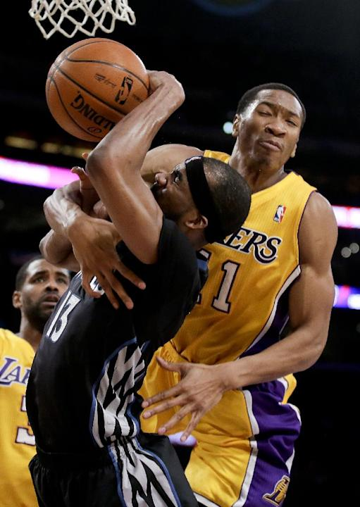 Los Angeles Lakers shooting guard Wesley Johnson, right, fouls Minnesota Timberwolves small forward Corey Brewer during the second half of an NBA basketball game in Los Angeles, Friday, Dec. 20, 2013
