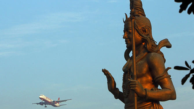 A statue of Hindu God Shiva stands in the foreground as a Kingfisher Airlines flight approaches the Indira Gandhi International airport in New Delhi, India, Friday, Nov. 11, 2011. Kingfisher, which is partly owned by brewery tycoon Vijay Mallya, has canceled more than 120 flights this week as pilots and crew called in sick after their October salaries were delayed. (AP Photo/ Gurinder Osan)