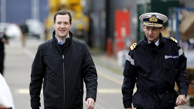 Britain's Chancellor of the Exchequer Osborne walks along the jetty at the Royal Navy's submarine base at Faslane