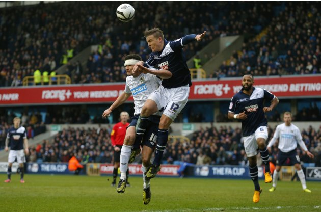 Lowry of Millwall and Dann of Blackburn Rovers jump for the ball during their English FA Cup quarter-final soccer match in London