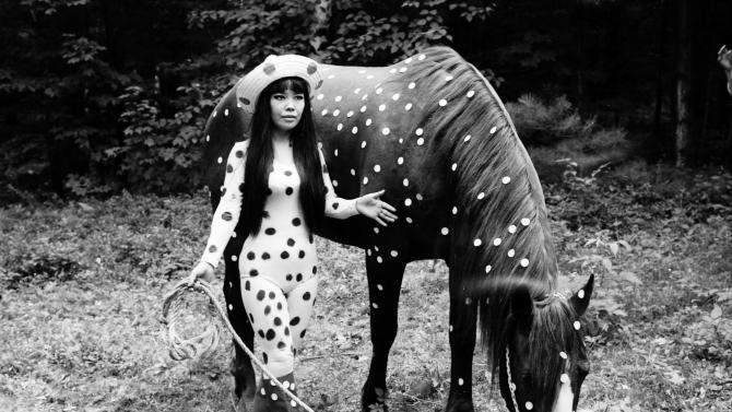 "In this 1967 photo released by Yayoi Kusama Studio Inc., Japanese artist Yayoi Kusama poses with a horse in a happening titled ""Horse Play"" in Woodstock, New York. Kusama's signature splash of dots has now arrived in the realm of fashion in a new collection from French luxury brand Louis Vuitton - bags, sunglasses, shoes and coats. The latest Kusama collection is showcased at its boutiques around the world, including New York, Paris, Tokyo and Singapore, sometimes with replica dolls of Kusama. (AP Photo/Yayoi Kusama Studio Inc.) NO SALES, EDITORIAL USE ONLY, CREDIT MANDATORY"