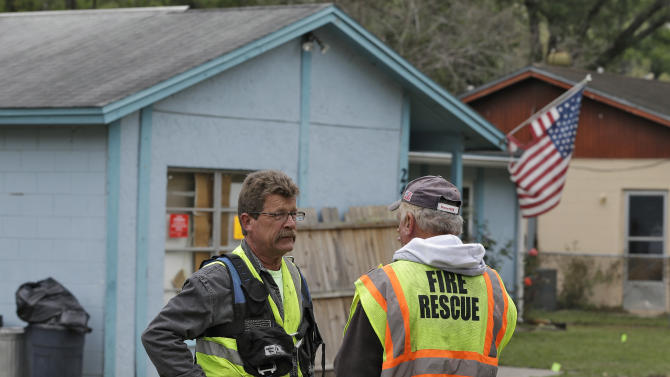 Engineers talk in front of a home, where a sinkhole opened up underneath a bedroom late Thursday evening and swallowed a man, in Seffner, Fla. on Saturday, March 2, 2013.   Jeffrey Bush, 37, was in his bedroom Thursday night when the earth opened and took him and everything else in his room. Five other people were in the house but managed to escape unharmed. Bush's brother jumped into the hole to try to help, but he had to be rescued himself by a sheriff's deputy.  (AP Photo/Chris O'Meara)