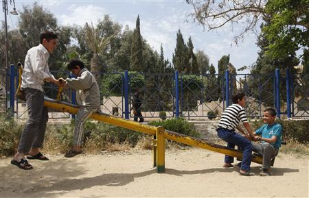File photo of a member of the Free Syrian Army as boys play on a seesaw in a public park in Raqqa province, east Syria