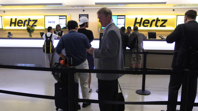 FILE - This May 9, 2011 file photo shows customers waiting in line at a Hertz rental car counter at San Jose International Airport in San Jose, Calif. Car rental agencies sometimes don't have enough cars to meet the demand. If there are no cars left at its airport rental facility, Hertz will let customers rent from a competitor and pay the difference, or pay for a cab to and from your hotel. (AP Photo/Paul Sakuma, file)