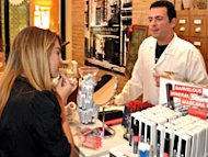 A customer in L'Oreal-owned Kiehl's applies makeup. The natural skin care line comes to Brazil this spring.